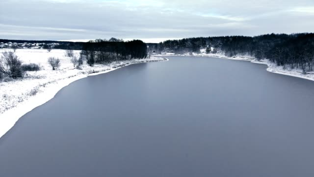flight over the snow forest and the frozen lake in the first snow - vídeo