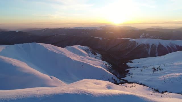 flug über den verschneiten bergen von der abendsonne beleuchtet - kieferngewächse stock-videos und b-roll-filmmaterial