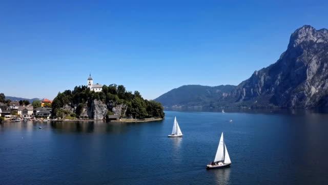 vídeos de stock, filmes e b-roll de voo sobre traunkirchen igreja no lago traunsee, em salzkammergut, áustria. - áustria