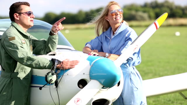 Flight School Flight instructor explains the flight plan on the map to a young woman who wants to become a pilot. propeller airplane stock videos & royalty-free footage