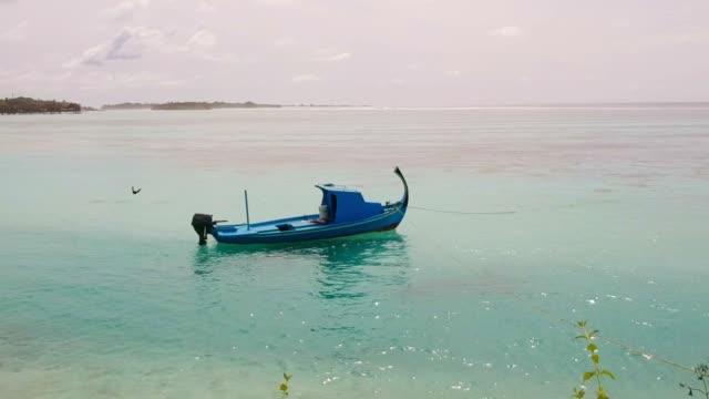 colpi di volo verso una barca di legno blu - isole mauritius video stock e b–roll
