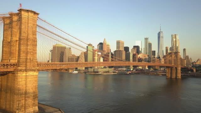 항공: 맨해튼과 이스트 리버 가 보이는 일출/선셋(4k)을 감상하며 브루클린 브리지로 비행 - 스카이라인 스톡 비디오 및 b-롤 화면