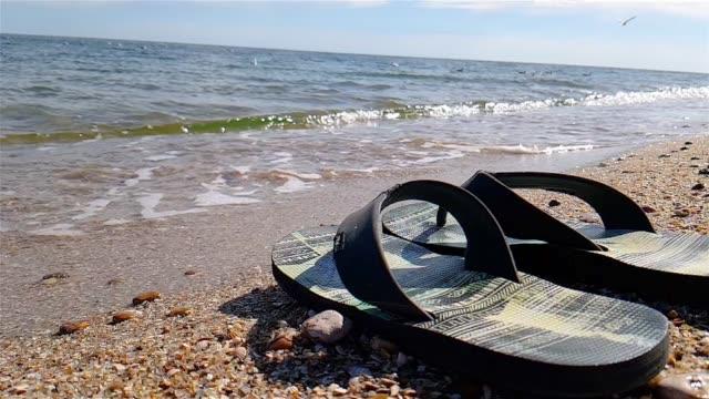 Flip-flops stand on the seashore, Black Flip-flops on the beach