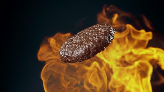 patty di hamburger di manzo alla brace capovolta che gira in fumo e fiamme al rallentatore - hamburger video stock e b–roll