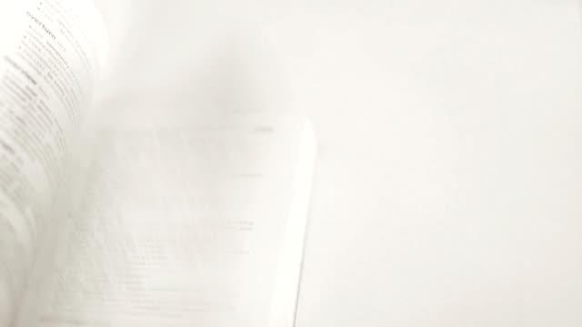 vidéos et rushes de regardant un livre sur fond blanc. - conseiller(ère) pédagogique