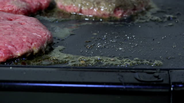 Flipping a gourmet hamburger on a grill close up