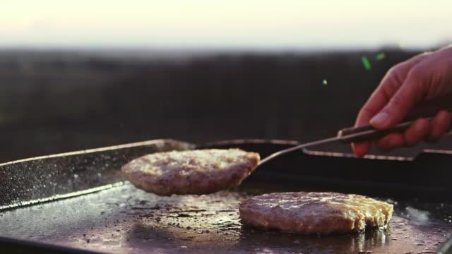 slo mo vändning hamburgare på en grill-tallrik - frying pan bildbanksvideor och videomaterial från bakom kulisserna