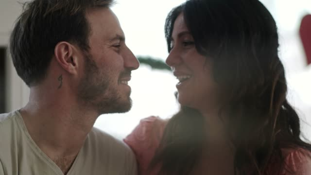 Flirtatious whispers and romantic kisses on Valentine's day Close up video of affectionate couple sitting in embrace and man flirtatiously whispering into his wife's ear after which they kiss and share a romantic moment on Valentine's day. anniversary stock videos & royalty-free footage