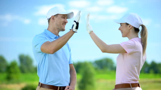 Flirting female and male golf players giving high-five after game, sympathy
