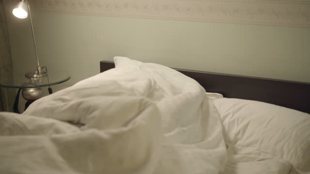 flirta man och hustru leende och gömmer sig under täcke ligger i sängen hemma. positiv glad kaukasiska man och kvinna njuter helger i sovrummet inomhus. kärlek och äktenskap koncept - duntäcke bildbanksvideor och videomaterial från bakom kulisserna