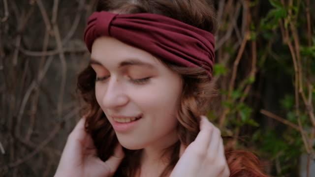 vidéos et rushes de femme de sourire flirty jouant le cheveu élégant à la mode - soins capillaires