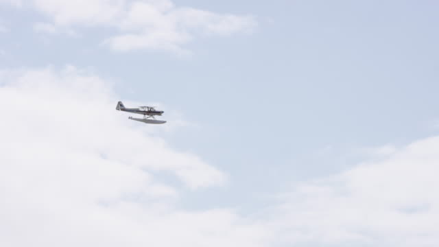 UHD 4K SLOMO: Float airplanes flying in and out of a lake on a summer afternoon Float airplanes flying in and out of a lake on a summer afternoon propeller airplane stock videos & royalty-free footage