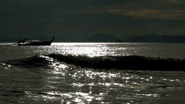 floating boat on a sunset on the sea. with sound - sky diving video stock e b–roll