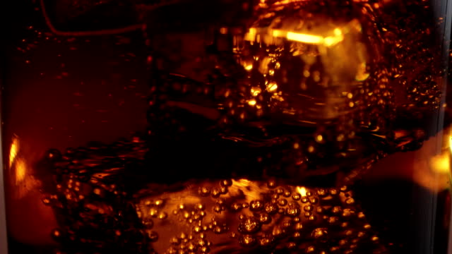 floating ice cubes in a glass of cola - close up macro shot in slow motion - soda pop stock videos & royalty-free footage
