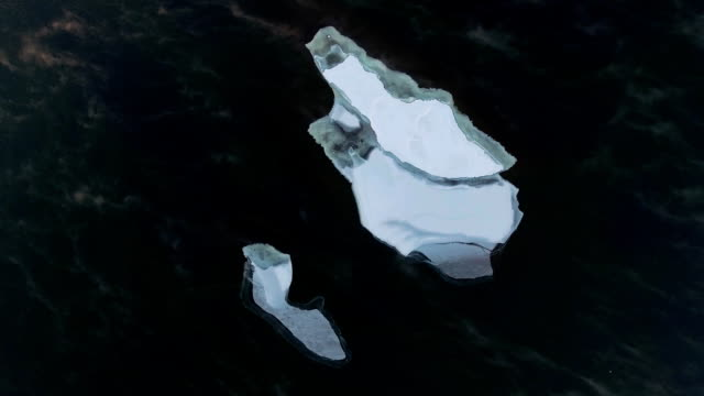 Floating ice drifts in open water, a quadrocopter. White ice floe Large ice floe sails in the midst of dark water, shot from above. ice drifts in open water, a quadrocopter. icecap stock videos & royalty-free footage