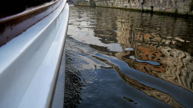 galleggiare su una barca sul canale in città lungo le mura di pietra. - bruges video stock e b–roll