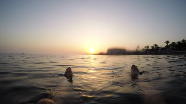 Floating in a calm beach at sunset in summer - First person view