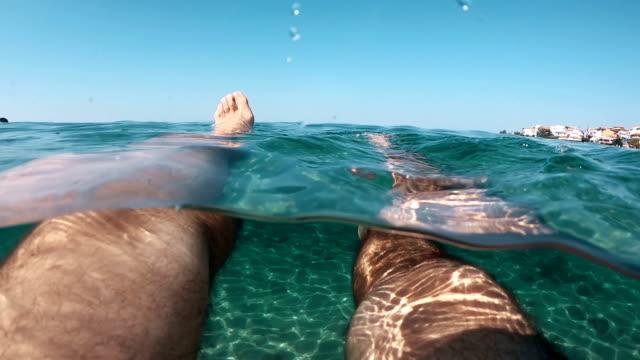 vídeos de stock, filmes e b-roll de flutuando no mar - perna termo anatômico