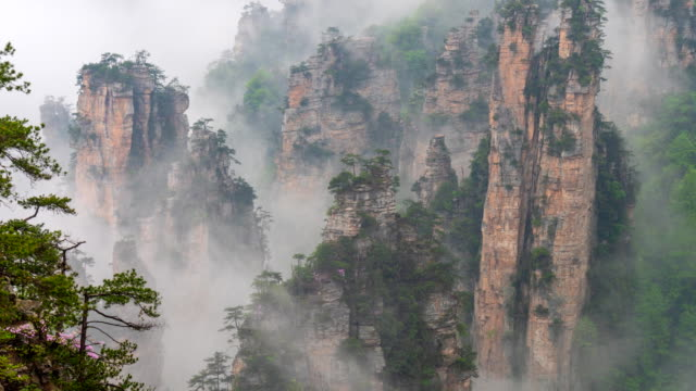 floating mountains in zhangjiajie forest park, china. time lapse shot. 4k - объект мирового наследия юнеско стоковые видео и кадры b-roll