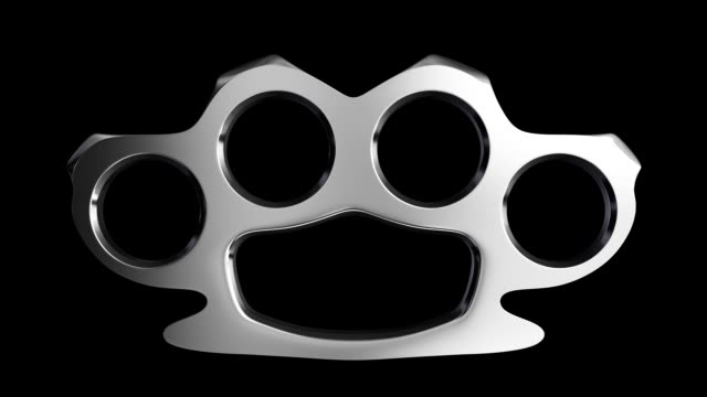 Floating steel knuckle duster with looping rotation on a black background including alpha matte. video