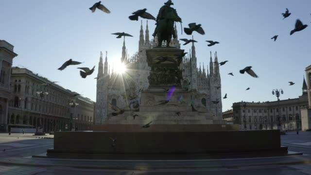 vídeos de stock e filmes b-roll de flock of pigeons flying in front of the duomo di milano (milan cathedral) in piazza del duomo (duomo square) in front of the statue of vittorio emanuele ii during the pandemic lockdown in 2020. empty city in the morning. - covid flight