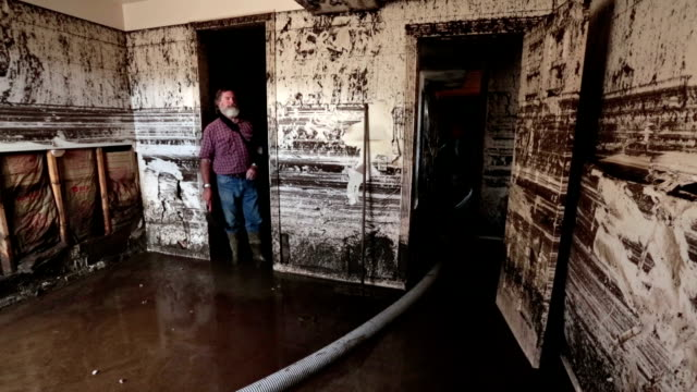 Flood basement man walks through room in mud water HD video