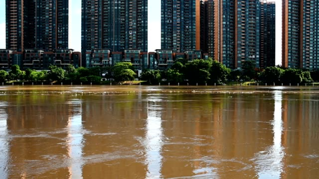 flood with lots of man made trashes floating with buildings at background - vídeo