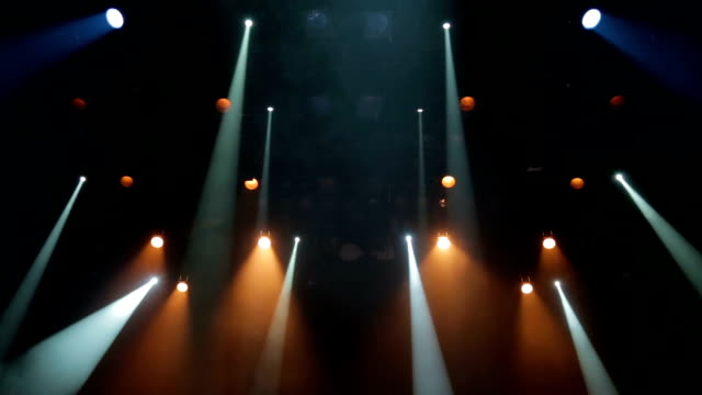 Floodlights, head, scanners, the theatrical smoke on the stage of the theatre during the performance. Lighting equipment. The lighting effects. Dynamic light video