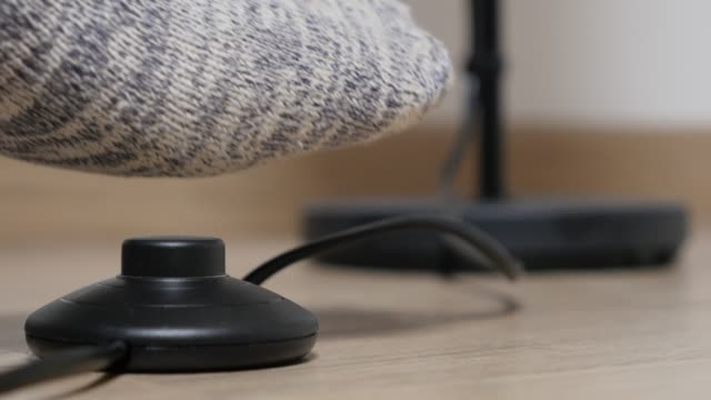 Floor stand lamp foot switching on and off close-up on button 4K