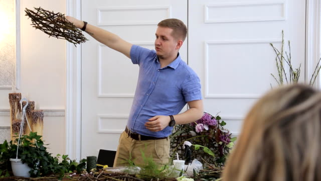 Floral designer holds studying courses of florists in art studio video