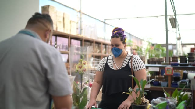 Florist and customer buying at a garden shop wearing a face mask