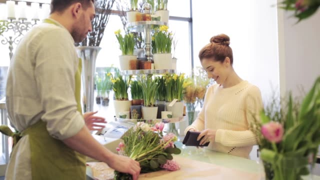 florist och kvinna köper blommor på blomsteraffär - liten bildbanksvideor och videomaterial från bakom kulisserna