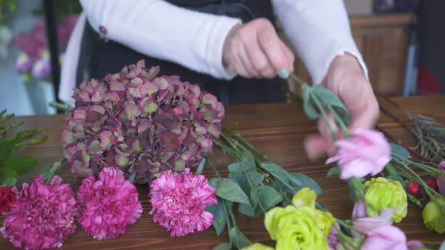 Florist arranging flowers on shop counter