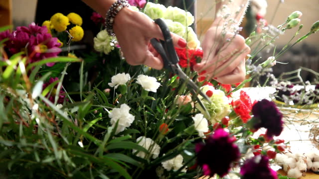 Florist at work choosing flowers for bouquet. video