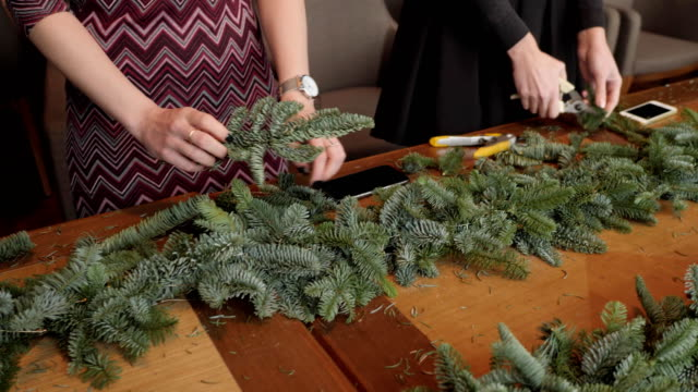 Florist at work: woman hands making christmas decorations garland of fir Nobilis. Happy new year dinner feast video