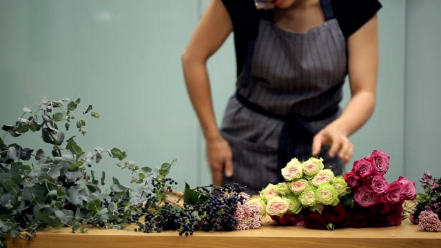 Florist cleans table for new bouquet and takes the order by phone video