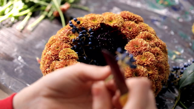 Florist collect composition of orange chrysanthemums, branches of viburnum video