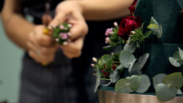 Florist decorates bouquet basis with beautiful small flowers video