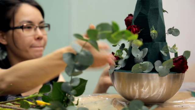 Florist decorates bouquet basis with green branches and ruby roses video