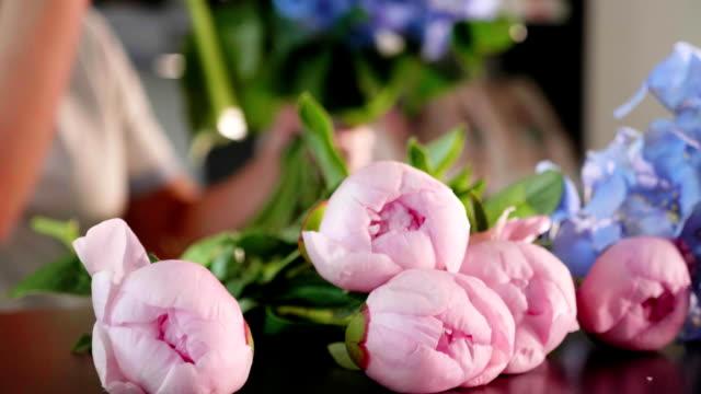 vídeos de stock e filmes b-roll de florist girl makes a bouquet in a flower salon, close-up - molho arranjo