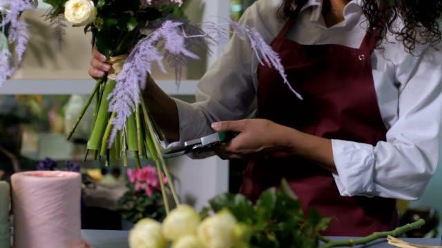 vidéos et rushes de mains de fleuriste coupant des tiges de fleur dans l'atelier - composition florale