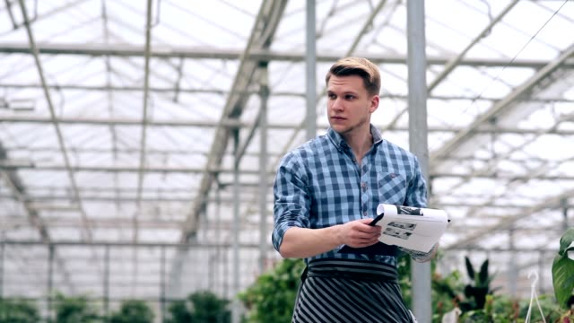 Florist holding accounting of plants in greenhouse video