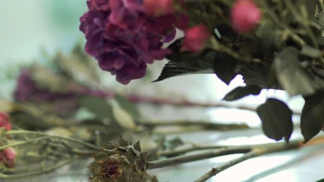 vidéos et rushes de fleuriste en fait un bouquet à la boutique de fleurs. femelle mains cueillette fleurs dans un bouquet. - composition florale