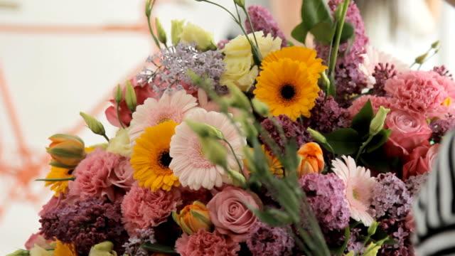 fiorista rende un enorme bellissimo bouquet multicolore composto da diversi fiori - nastro per capelli video stock e b–roll