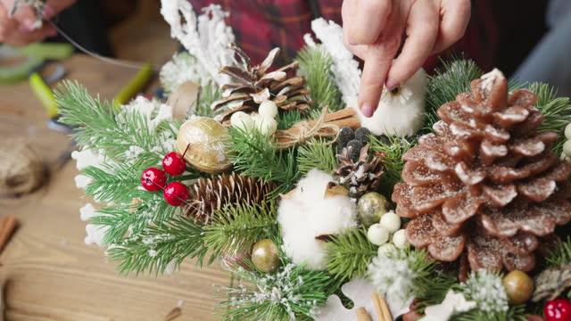 florist stellt weihnachtskorb mit roten beeren, tannenzweigen und nadelzapfen - selbstgemacht stock-videos und b-roll-filmmaterial