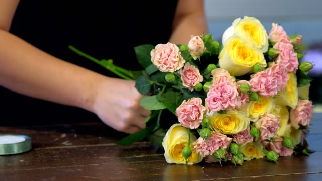 Florist makes creates bouquet ties roses stems with ribbon, hands closeup. Floral business concept. Professional woman florist works makes bouquet ties roses stems with ribbon at table in flower shop, hands closeup. Creates bunch composition in floristic studio store. bunch stock videos & royalty-free footage