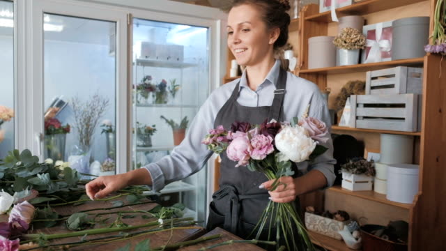 Florist making fresh flower bouquet in flower shop