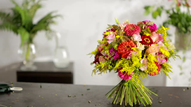 Florist prepares a bouquet of flowers for sale to customers video