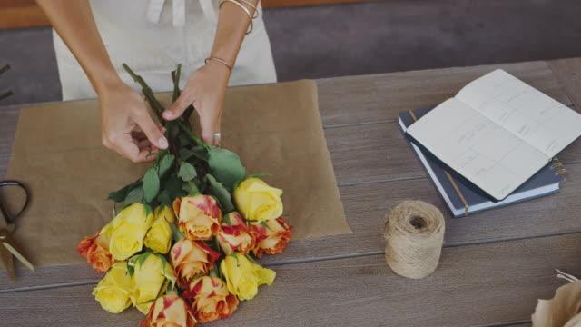 vidéos et rushes de fleuriste préparant le bouquet de fleur - bouquet formel