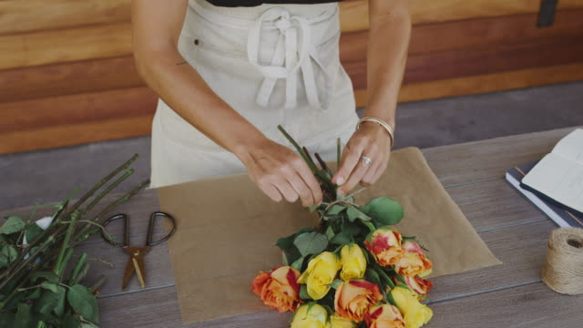florist preparing flower bouquet - bouquet video stock e b–roll